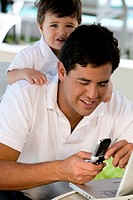 Close-up of a father using a mobile phone with his son standing behind him