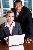 Portrait of a businessman and a businesswoman in front of a laptop