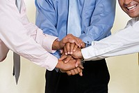 Close-up of three businessmen shaking hands