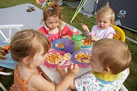 4 children camping, sitting round a table eating dinner, one is feeding the little baby.