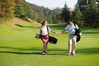 Couple holding hands as they walk down the fairway