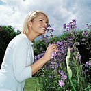 Blond woman smelling flowers