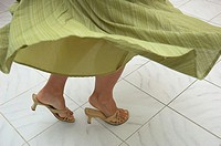 Young woman´s legs in a dance motion on tile floor