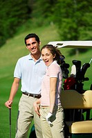 Couple smiling besides a golf cart