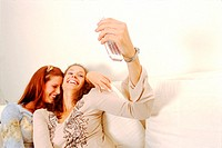 Two young women on a couch looking at a mobile phone