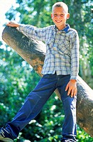 Portrait of a young boy standing on tree branch