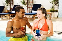 Close-up of a young couple holding glasses in a swimming pool