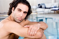 Side profile of a mid adult man sitting at the poolside