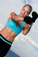 Low angle view of a young woman wearing boxing gloves