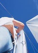 Low angle view of young woman reefing sails on sailboat
