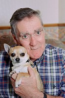 Portrait of man with Alzheimer´s disease holding pet dog,