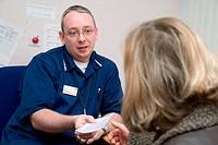 Authorised Nurse handing prescription to patient, NHS Walkin Centre Nottingham,
