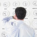 Businessman checking watch with time zone clocks on the wall behind him