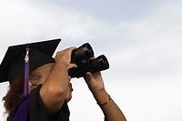 Female graduate looking through binoculars