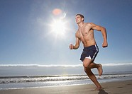 Man without shirt running at beach