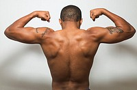 Rear view of man´s bare back flexing muscles