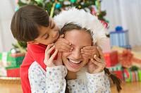 Boy covering older sister´s eyes on Christmas