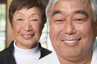 Senior Asian couple with man in foreground