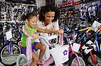 Mother helping young daughter with bike in bike shop