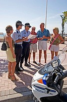 Local police informing a group of tourists in Fuengirola promenade. Málaga province. Costa del Sol. Andalusia, Spain