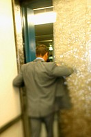 Rear view of a businessman opening the door of an elevator