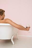 Man lying in bathtub, holding a wine glass, rear view