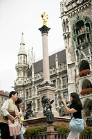 Young Asian woman taking a picture of an Asian heterosexual couple under the golden statue of the Virgin Mother