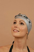 A female swimmer wearing a bathing cap and goggles