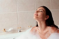 Close-up of a young woman taking a bubble bath
