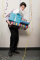 Businessman struggling with pile of presents