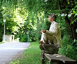 Man sitting on park bench, meditating