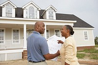 African American couple reading house plans in front of new house