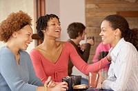 Three female friends in cafe drinking coffee