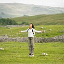 Young woman standing on a rock with her arms outstretched in rural location,