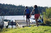 Couple carrying canoe out to lake