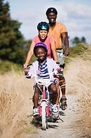 Family riding bikes on dirt trail