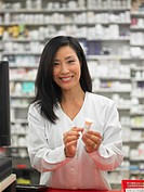 Female employee displaying a bottle of pills for the camera