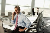 Businessman talking on cell phone in conference room