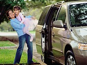 Mother picking her daughter up out of the car