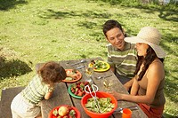 Family eating on a picnic table outdoors