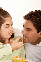 Close-up of a girl feeding her father a strawberry