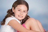 Close-up of a girl hugging her knees
