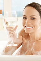Portrait of a young woman holding a glass of white wine in the bathtub