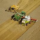 Combine harvesting on agricultural field, aerial view. Skåne. Sweden.