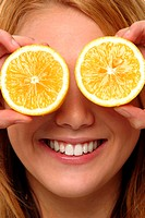 A woman with a smile using two slices of orange to cover her eyes