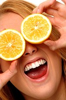 A woman laughing while using two slices of orange to cover her eyes