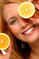 A woman holding two slices of orange with one covering her left eye