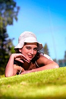 A woman with a white hat posing by lying on the grass