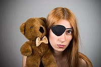 Young woman, with long red hair, wearing an eye patch and holding a stuffed animal on her shoulder