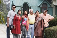Portrait of a mature couple and their four children standing in front of a house